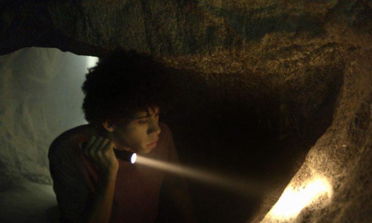 """Feijão (Cauê Campos) encontra desenhos e artefatos em gruta misteriosa em """"O Sétimo Guardião"""""""